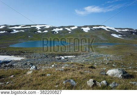 Swedish Lapland landscape with stones, snow and fragile vegetation. Arctic environment of Scandinavia in warm summer sunny day with blue sky. Nordkalottruta or Arctic hiking Trail in northern Sweden
