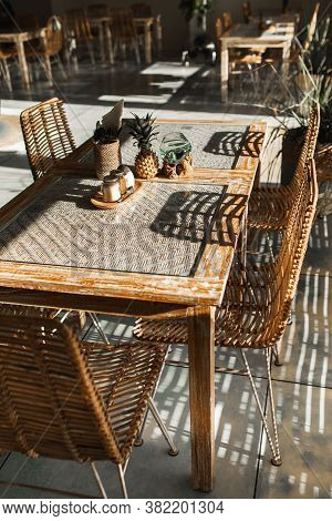 Wicker Rattan Handmade Chairs And Wooden Table. Trendy Furniture Design. Summer Cafe Terrace.