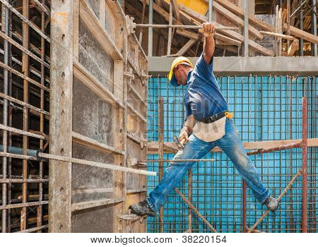 Construction Worker Balancing Between Scaffold And Formwork Frame