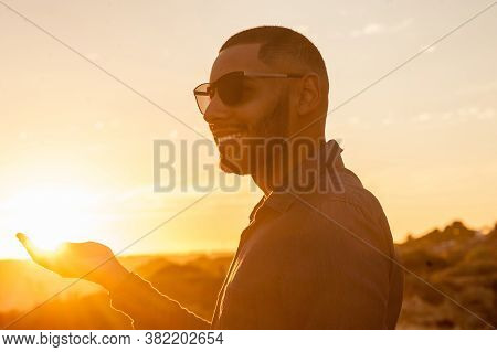 Happy Latin Man Walking And Enjoying The Sunset With A Natural Landscape View