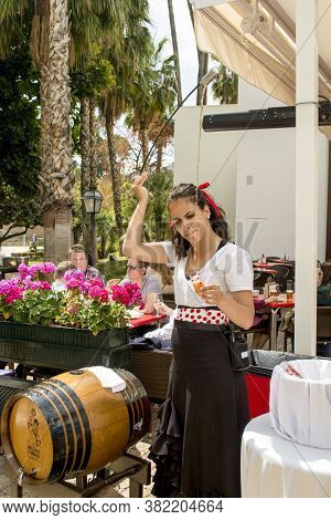 Waitress Serving And Pouring Sherry, A Traditional Habit Called Venenciar In Malaga, Spain