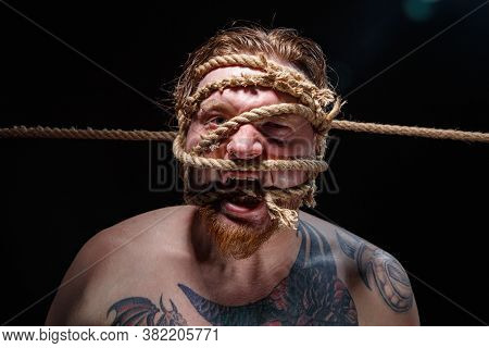 Image Of Binded Tattooed Screaming Man With Rope On Face