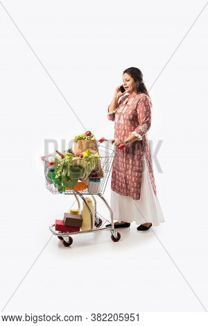 Happy Indian Woman With A Shopping Cart. Isolated Over White Background