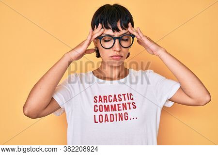 Beautiful brunettte woman wearing sarcastic comments loading t-shirt suffering from headache desperate and stressed because pain and migraine. hands on head.