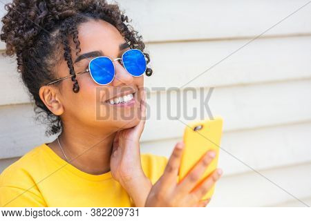 Girl teenager teen female young African American mixed race biracial woman outside smiling with perfect teeth wearing blue sunglasses and using a mobile cell phone for social media