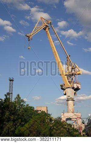 Marine Commercial Industrial Port. Abandoned Industrial Shipbuilding Crane. Yellow Marine Crane