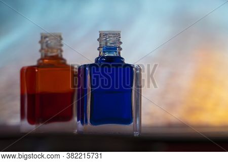 Two Bottles Of Aurasoma With A Red And Bluu Essence Against An Abstract Background.