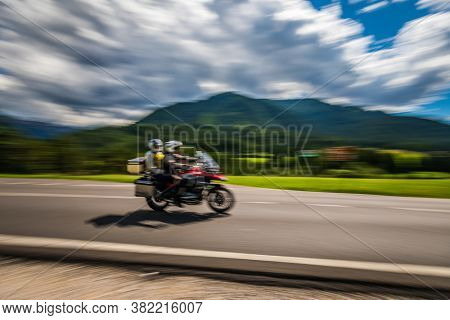Blurred motion Couple Bikers riding a tricycle on the road.