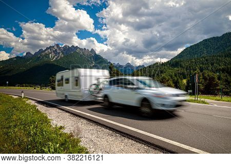 Family vacation travel, holiday trip in motorhome RV, Caravan car Vacation. Beautiful Nature Italy natural landscape Alps. Warning - authentic shooting there is a motion blur.