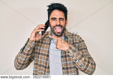 Handsome hispanic man with beard having conversation talking on the smartphone sticking tongue out happy with funny expression.