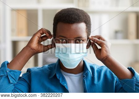 Head Ad Shoulders Portrait Of Young African-american Man Putting On Face Mask While Working In Post