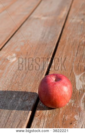 Freshly Picked Red Apple On Weathered Picnic Table