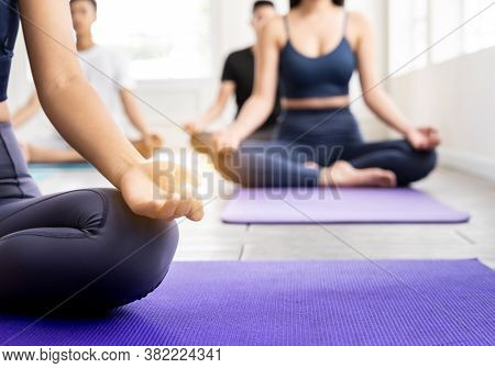 Close up of sporty attractive asian coach on Lotus pose position sitting Padmasana with background of student practicing yoga lesson. Work out fitness healthy lifestyle concept