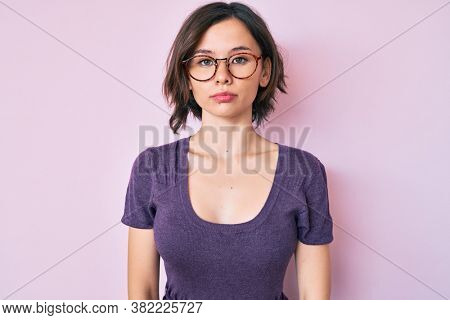 Young beautiful woman wearing casual clothes and glasses with serious expression on face. simple and natural looking at the camera.