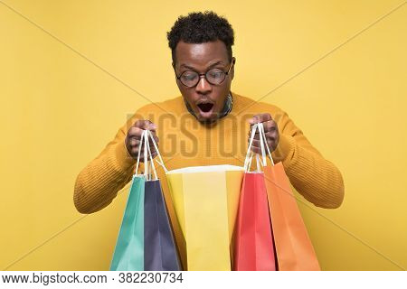 Shocked African Young Man Holding Shopping Bags Being Surprises.