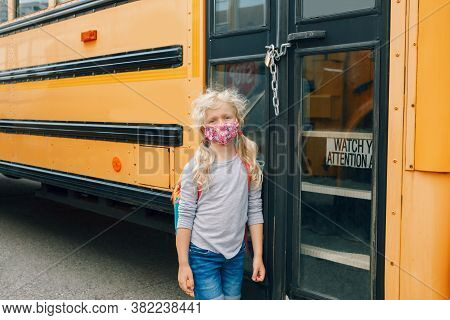 Sad Girl Student With Face Mask Near Locked Yellow Bus. Closed School During Pandemic Lockdown And Q