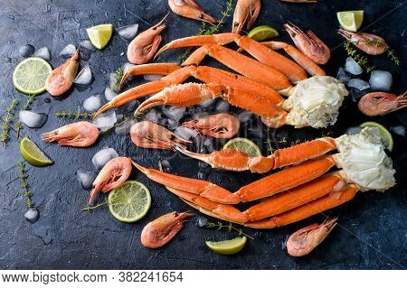 Fresh Crab Claws, Lime, , Ice, Shrimp, Vegetables On A Dark Background. Delicious Seafood, Healthy F