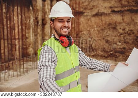 Cheerful Male Builder In Helmet And Waistcoat Smiling And Looking At Camera While Examining Blueprin