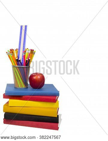 Vertical Shot Of A Stack Of Colorful Books With An Apple And A Wire Pencil Holder Sitting On Top.  P