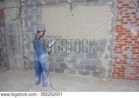 Machine Application Of Plaster To The Wall. Plasterer Spraying Plaster On Wall. Professional, Painti