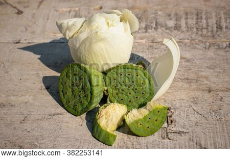 Nelumbo Nucifera Pods Or Indian Lotus Pods With Flower On Wooden Surface