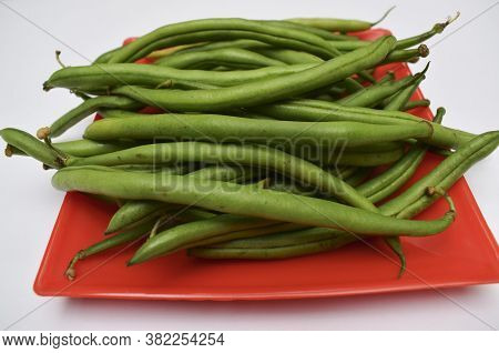 Fresh French Beans Indian Vegetables Oon Red Plate With White Background. Green Beans Bunch Many Veg