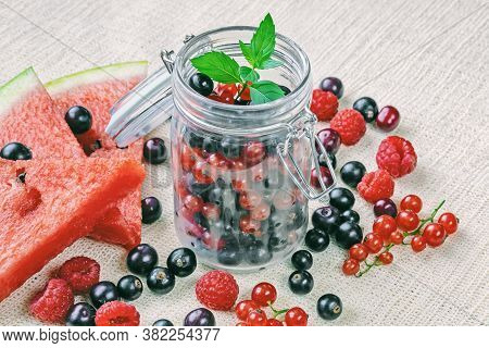Glass Jar With Fresh Currant Berries, Raspberries, Watermelon Slices And Mint Leaves On Linen Textil