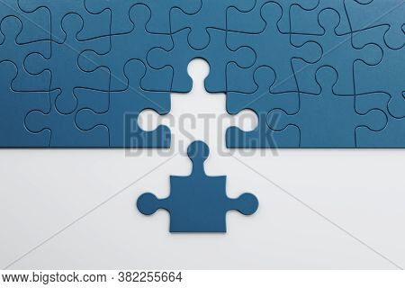 Incomplete Blue Puzzles On White Table. Business And Teamwork Concept. 3d Rendering