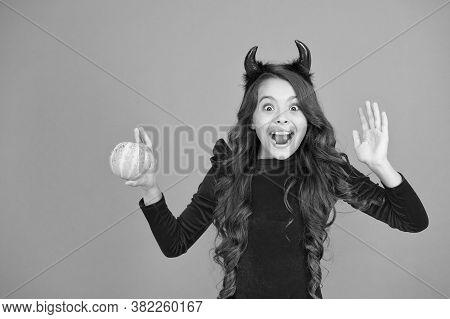 Evil Demon. Little Demon Of Child Orange Background. Happy Girl With Red Demon Horns Hold Pumpkin. D