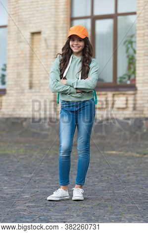 Discover Cool Trends. Happy Child Keep Arms Crossed Outdoors. Little Girl With Cool Look. Fall Fashi