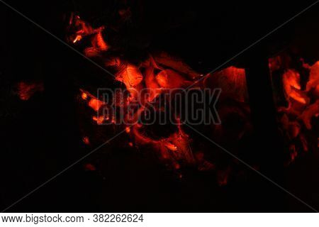 Red Embers Of Hot Fire On Blurred Background Of Darkness