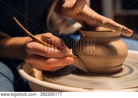A Master In A Pottery Workshop Shows The Technique Of Modeling A Pot On A Potters Wheel