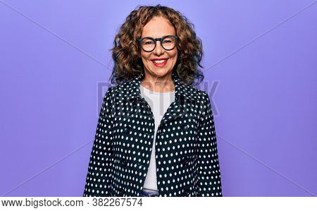 Middle age beautiful woman wearing casual coat and glasses over isolated purple background with a happy and cool smile on face. Lucky person.