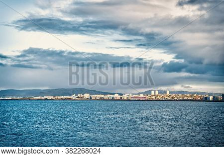 City On Sea Coast Iceland. Scandinavian Seascape Concept. Calm Water Surface And City With High Buil