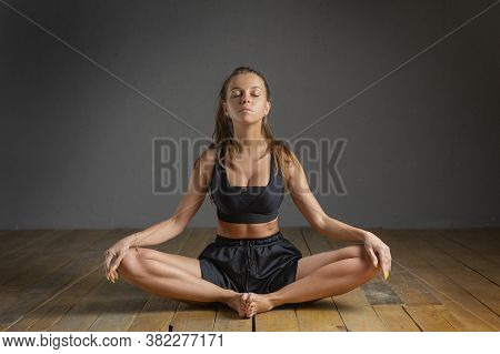 Young Woman Practicing Yoga Sitting In Lotus Pose And Meditating In Dark Room.