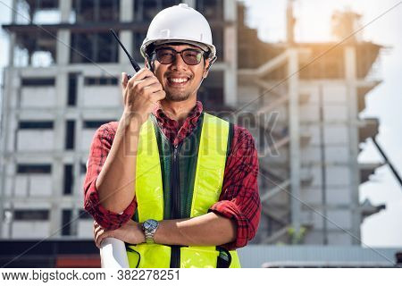 Asian Young Engineer Smiling Wear A Safety Helmet Equipment And Drawing On Hand With Radio Communica