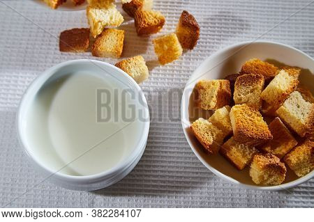 Square Toasted Pieces Of Homemade Delicious Rusk, Hardtack, Dryasdust, Zwieback And Plate Of Milk On