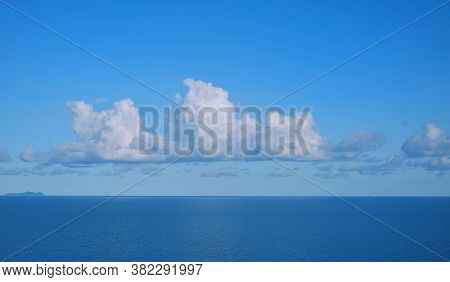 View Of A Calm Blue Sea With White Fluffy Clouds And Clear Blue Sky On A Sunny Day In Early Morning