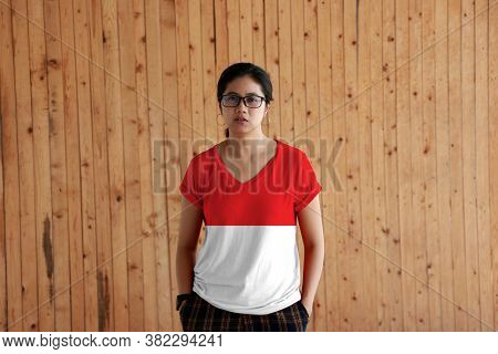 Woman Wearing Indonesia Flag Color Shirt And Standing With Two Hands In Pant Pockets On The Wooden W