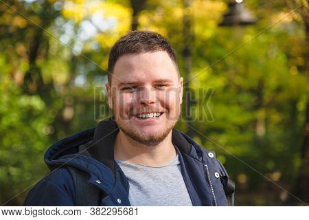 Young Smiling Man Portrait At City Autumn Park