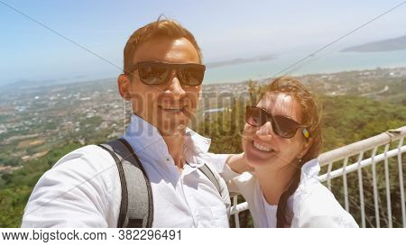 Beautiful Couple Stands On Hilltop And Makes Selfie Against Pictorial Cityscape Silhouette And Blue