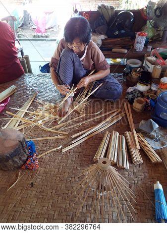 Bor Sang, Chiang Mai, Thailand, December 22, 2018: Craftswoman Cutting Bamboo To Make Umbrellas At B
