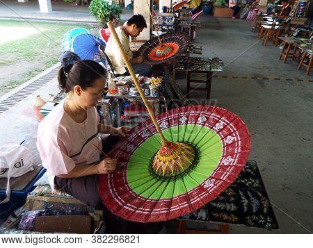 Bor Sang, Chiang Mai, Thailand, December 22, 2018: Craftsmen Painting Umbrellas At The Bor Sang Umbr