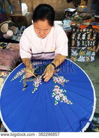 Bor Sang, Chiang Mai, Thailand, December 22, 2018: A Woman Colors An Umbrella At The Bor Sang Umbrel
