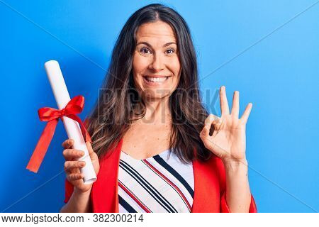 Young beautiful brunette smart woman holding graduated degree diploma over blue background doing ok sign with fingers, smiling friendly gesturing excellent symbol