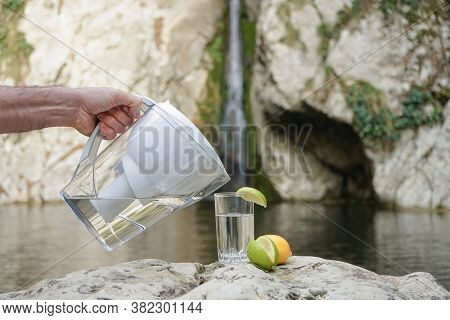 Water Pitcher. A Man Uses A Jug With A Filter To Purify Water Against The Background Of A Mountain R