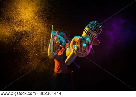 Singing With Microphone. Young Woman With Smoke And Neon Light On Black Background. Highly Tensioned