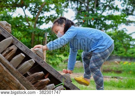 A Cute Young Asian Girl Wearing A Surgical Mask, Climbing Up A Wooden Steep Ramp At A Park, Grabbing