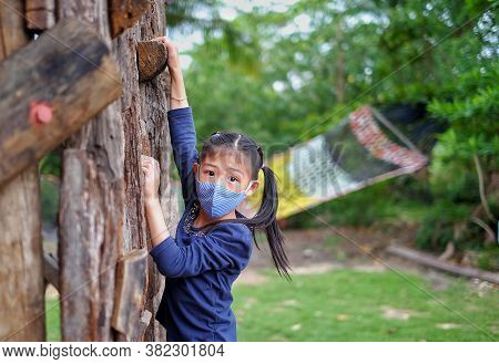 A Cute Young Asian Girl With A Face Mask Is Climbing A Wall Of An Obstacle Course, Being Brave But C