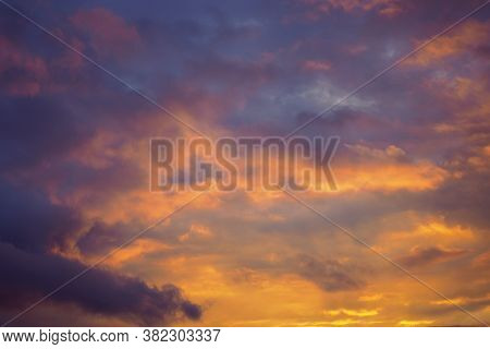 Cloudy Sky At Sunset. Dark Violet-yellow Natural Background Or Wallpaper. The Rays Of The Setting Su